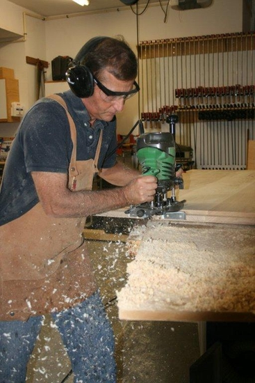 Ron routing a tongue on a maple table